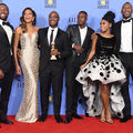 Six Black women and men standing against light blue background with dark blue text, with one Black man holding gold statue and one Black woman wearing a gold gown