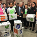 Women hold boxes of petitions