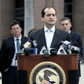 Brown man in black suit white pinstripes and blue tie stands behind brown podium with multicolored microphones, in front of five individuals in black and navy suits