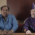 Black man in blue shirt seated next to White Ku Klux Klan member in purple robes and hood with red and white insignia, in front of two-toned brown wall