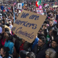 """Crowd of protestors, one holds sign that says, """"We are workers, not criminals."""""""