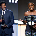 Black man in navy suit holding gold award statue behind black microphone and stand, in front of navy screen; Black woman in green, blue, black and white dress holding gold statue behind black microphone and stand, in front of gold and black screen