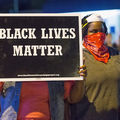 Black woman in blue denim vest and pink t-shirt holds black sign with white text while standing next to Black woman in green shirt and red bandanna and white mask