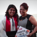 Teenage girl in graduation robes poses with mother