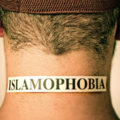 """Back of someone's head, with label that reads, """"Islamophobia"""" on the nape of the person's neck"""
