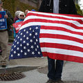 A demonstrator holds an upside down American flag during a protest near the site of a fundraiser attended by former President Barack Obama on April 3, 2013, in San Francisco, California.