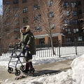 A Black woman with a walker passes by a brown housing project on a snowy day
