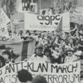 Black-and-white photo of Black, Brown and White people holding banners during a march