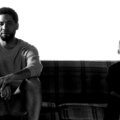 Black-and-white image of a Black man in a white shirt and shorts seated on a plaid couch next to a Black boy in a black shirt and dark pants against white background