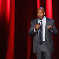 Black man in grey suit with light blue shirt and navy tie hold black microphone in front of red curtain