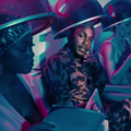 Kendrick Lamar sits beside women who are under hair dryer hoods