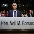 "Man sits at table behind placard that reads ""Hon. Neil Gorsuch."""