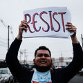 """Man holds sign that reads, """"Resist."""""""