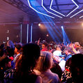 Multiracial crowd stands under blue neon light and black ceiling