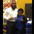 Black man in white shirt and grey pants next to Black girl in blue shirt and black sweater and pants, holding blue flag with white text in front of blue table and orange wall with orange, white and black tiger painting