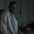 Black man in grey sweatshirt in front of white wooden kitchen storage doors, behind brown wood doorway