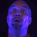 Man's startled face, bathed in blue light
