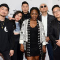 Asian man in black outfit next to Asian woman in blue-white shirt and black pants next to Asian man in black sweatshirt next to Brown woman in black-and-white sweater and black dress next to Asian man in black outfit next to Asian man in black outfit