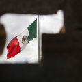 Mexican flag. Red, green and white flag viewed through a hole in a brick wall