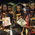Black women in black and yellow commencement robes and black, green, gold and red stoles in crowd of similarly attired Black women and men