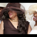 Black man in brown suit and beige hat next to Black woman in dark brown dress and hat next to Black woman in white dress and beige hat