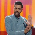Brown man in blue shirt in front of yellow and purple screen and black background