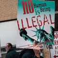 "Person holds sign that reads, ""No human being is illegal."""