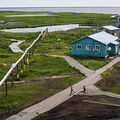 People walk down the elevated, raised wooden sidewalks, which were created so people don't sink into the melting permafrost, on July 5, 2015, in Newtok, Alaska. This village has to relocate due to melting permafrost and rapid erosion of a nearby river.