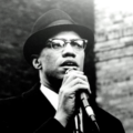 Black-and-white photo of Black man in dark coat, light hat and white shirt in front of grey stone wall