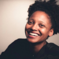Black woman smiling in black sweater in front of brown background