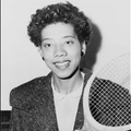 Black-and-white photo of Black woman holding brown tennis racket in white clothing