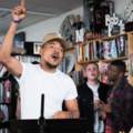 Black man in white t-shirt and light brown baseball cap in front of Black woman in blue jacket, White man in black jacket, Black man in red-and-black flannel shirt and Black man in pink hoodie in front of bookshelves and grey wall