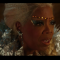 Black woman in blue eye makeup and gold eyebrow jewelry and grey outfit in front of blurry brown background