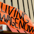 "Sign reads: ""Living wage now."""