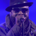 Black man in brown fedora and sun glasses with dark green jacket and spotted bandana in front of blue screen
