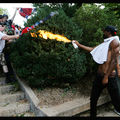 Black man in black pants with white shirt and black hat stands next to White man and Black man holds white can with orange flames at White men in black and white clothing holding red and white and blue Confederate flags