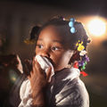 A little Black girl wearing colorful barrettes holds a rag in front of her mouth to block police tear gas during a protest against the killing of Michael Brown