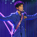Black man in purple suit wearing purple guitar while bathed in blue light