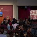 White woman in blue suit at brown podium speaks to crowd including Brown teenage girl in grey sweatshirt and blue jeans
