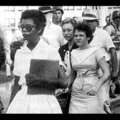 Black-and-white image of Black woman in white dress and black sunglasses walking in front of White people in white and grey clothes