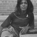 Black woman in black sweater and grey skirt sitting on grey concrete steps in front of brick wall and grey screen door
