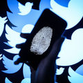 In this photo illustration, a thumbprint is displayed on a mobile phone as the logo for the Twitter social media network is projected onto a screen