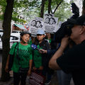 """Two women in green t-shirts talk to a reporter as people behind them hold black and white signs that say """"Justice for Edith and Shirley."""""""