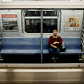 An Asian woman wearing a maroon shirt sits on a New York City subway train