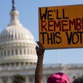 """Protestors, one holds sign that says, """"We'll remember this vote."""""""