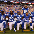 Black men in blue uniforms with white lettering take knees and lock arms in front of other men in blue uniforms and stadium with people in multicolored clothing