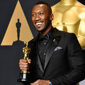 Black man in all-black tuxedo holds gold award statue in front of charcoal screen with gold insignias