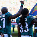 Black men in dark green jerseys with white lettering and numbers and white pants raise fists behind blurry blue flag and sunlit crowd