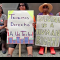 "Two protestors hold up signs. One of them says in Spanish, ""We Have Right to A Roof."" The other one says, ""Housing is a human right!"""