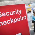 """In an airport, a red sign with white writing that says """"Security Checkpoint"""""""